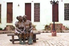 Paar in liefde die en bronsbeeldhouwwerk kussen koesteren royalty-vrije stock afbeeldingen