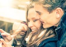 Paar in liefde die pret met Smartphone hebben Stock Afbeeldingen