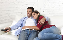Paar in liefde geknuffel op huislaag ontspannende het letten op film op televisie met de afstandsbediening van de mensenholding royalty-vrije stock foto's