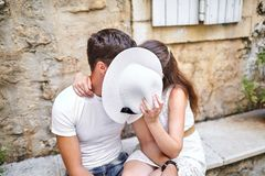 Paar in liefde het kussen achter witte vrouwelijke hoed op de steen benc royalty-vrije stock afbeeldingen