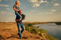 Paar in liefde Mensen dragend meisje op vervoer per kangoeroewagen Royalty-vrije Stock Afbeeldingen