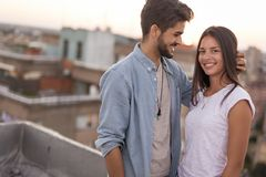 Paar in liefde op een de bouwdak bij zonsondergang royalty-vrije stock afbeelding
