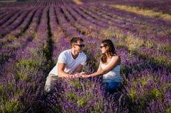 Paar in liefde op lavendelgebieden Jongen en meisje op de bloemgebieden stock afbeeldingen