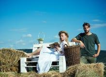 Paar in liefde op vakantie De vrouwenbruid in huwelijkskleding ontspant op bank Sensueel vrouw gelezen boek voor de mens De famil royalty-vrije stock afbeelding