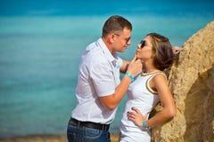 Paar in liefdeflirts op het strand De kerel houdt het meisje door een kin en trekt naar zich aan Stock Fotografie