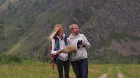 Paar in liefdereizen in de bergen met een kaart en verrekijkers de vriendenreizigers zoeken richtingen op stock videobeelden