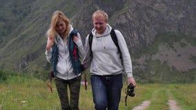 Paar in liefdereizen in de bergen met een kaart en verrekijkers de vriendenreizigers zoeken richtingen op stock video