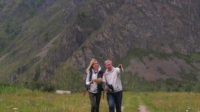 Paar in liefdereizen in de bergen met een kaart en verrekijkers de vriendenreizigers zoeken richtingen op stock footage