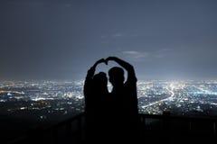 Paar in liefdesilhouet op de berg, de liefde en de valentijnskaarten c Stock Afbeelding
