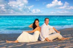 Paar in liefdezitting in blauw strand Stock Foto's