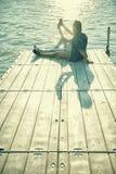 Paar in liefdezitting op de pijler, selfie stock foto
