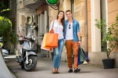 Paar lopen ongehaast samen met het winkelen zakken stock foto