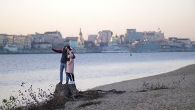Paar macht selfie auf dem Strand im Herbst vor dem hintergrund des Flusses und der Stadt 4K langsames MO stock video