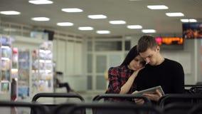 Paar, man en vrouwen de zitting in wachtkamer en kijkt in tablet stock videobeelden