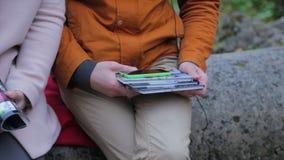 Paar of mens en wonam het letten van op iets op de telefoon in park Cople die op iets op een mobiele telefoon en een tablet lette royalty-vrije stock afbeelding
