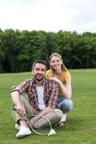 Paar met badmintonracketten en shuttle die op gras in park rusten royalty-vrije stock foto's