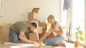 Paar met boekzitting op bed terwijl zich het bewegen in nieuw huis stock video