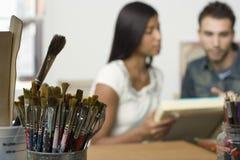 Paar met Canvases in Kunstenaar Studio stock afbeelding