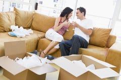 Paar met champagne door dozen in nieuw huis Royalty-vrije Stock Afbeeldingen