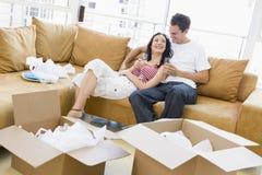 Paar met champagne door dozen in nieuw huis Stock Foto