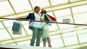 Paar met de kosten van Kerstmisgiften op een balkon en besprekingen De man en de vrouw die greeppakketten van giften omhelzen voo stock videobeelden