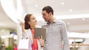 Paar met de zakken van tabletpc en het winkelen in wandelgalerij stock videobeelden
