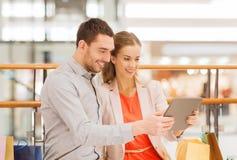 Paar met de zakken van tabletpc en het winkelen in wandelgalerij Royalty-vrije Stock Foto's