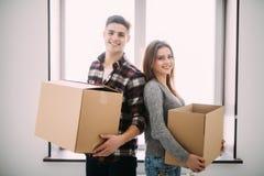 Paar met dozen die zich in het nieuwe huis glimlachen bewegen Jong paar bij het bewegen van dag royalty-vrije stock afbeeldingen