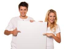 Paar met een lege affiche om het openen te adverteren Royalty-vrije Stock Fotografie