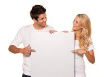 Paar met een lege affiche om het openen te adverteren Royalty-vrije Stock Foto