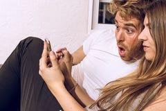 Paar met een verrast gezicht die de mobiele telefoon bekijken royalty-vrije stock foto