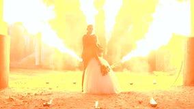 Paar met een vreselijke make-up voor Halloween-tribune tegen een brandende brand in dark stock footage