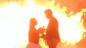 Paar met een vreselijke make-up voor Halloween-tribune tegen een brandende brand in dark stock videobeelden