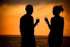 Paar met glazen op overzeese zonsondergang Stock Foto's
