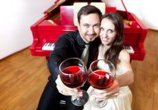 Paar met glazen wijn dichtbij piano Stock Fotografie