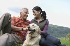 Paar met Golden retriever op Gras stock foto