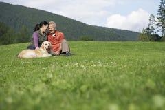 Paar met Golden retriever op Gras royalty-vrije stock foto's