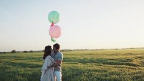 Paar met heliumballen die in een appeltuin lopen en handen houden bij zonsopgang Gefilmd in langzame motie stock footage