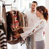 Paar met het kiezen van vest bij kledingswinkel stock foto