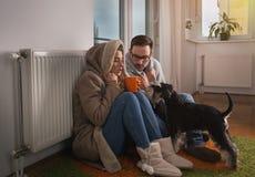 Paar met hondzitting naast radiator en het bevriezen stock afbeeldingen