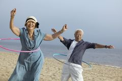 Paar met hulahoepels op strand Stock Afbeeldingen