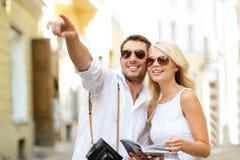 Paar met kaart, camera en reizigersgids Stock Afbeelding