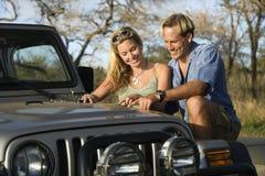Paar met Kaart op de Kap van de Auto Stock Afbeelding