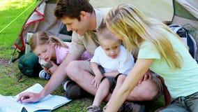 Paar met kinderen die een kaart kijken stock videobeelden