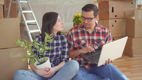 Paar met laptop op de achtergrond van dozen voor zich het bewegen, nieuw huis stock video