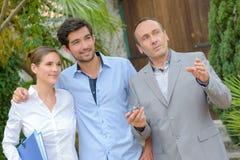 Paar met makelaar in onroerend goed het bezoeken huis voor verkoop royalty-vrije stock afbeelding