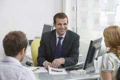 Paar met Makelaar in onroerend goed In Office stock afbeelding