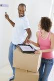 Paar met rol en verf in nieuw huis Stock Foto's