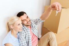 Paar met sleutel en dozen die zich aan nieuw huis bewegen Stock Afbeelding