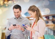Paar met smartphones en het winkelen zakken in wandelgalerij royalty-vrije stock foto's